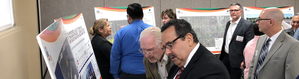 People reading Metrolink San Bernardino Line Double Track Project (Lilac to Rancho) banners